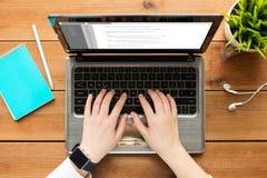 Chiuda su della donna o dello studente che scrive sul computer portatile fotografia stock