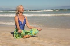 Chiuda su della donna senior che medita mentre si siedono sulla riva Fotografia Stock Libera da Diritti