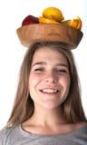 Chiuda su della donna sorpresa giovani quale sta tenendo una ciotola di legno con i frutti: mele, arance, limone Vitamine e cibo  Fotografia Stock