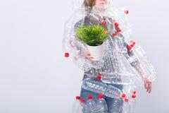 Chiuda su della donna sta stando con il vestito in bottiglie di plastica e sta tenendo la pianta verde Problema dell'inquinamento fotografie stock