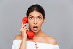 Chiuda su della donna stupita che parla sul tubo del telefono Fotografia Stock