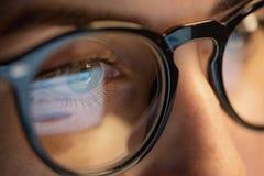 Chiuda su della donna in vetri che esaminano lo schermo fotografia stock