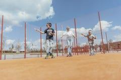 Chiuda su della famiglia di skateboarding al campo da giuoco Concetto 'nucleo familiare' felice fotografie stock libere da diritti