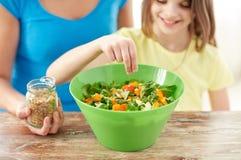 Chiuda su della famiglia felice che cucina l'insalata in cucina Fotografie Stock Libere da Diritti
