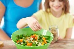 Chiuda su della famiglia felice che cucina l'insalata in cucina Immagini Stock
