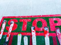 Chiuda su della fermata di parola che avverte agli sciatori che devono fermarsi a quel posto Alcune attrezzature dello sci con ne fotografia stock libera da diritti