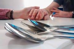 Chiuda su della fila dei cucchiai sulla tavola, con le mani tenute nel fondo Immagini Stock Libere da Diritti