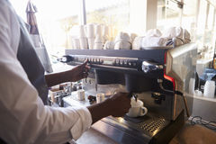 Chiuda su della ghiottoneria di Making Coffee In di barista facendo uso della macchina immagini stock libere da diritti