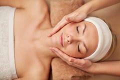 Chiuda su della giovane donna che ha massaggio di fronte in stazione termale Fotografia Stock