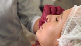 Chiuda su della giovane donna che prepara all'iniezione dell'acido ialuronico alle labbra video d archivio