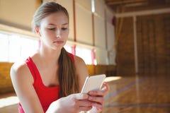 Chiuda su della giovane donna che utilizza il telefono cellulare nel campo da pallacanestro Fotografia Stock