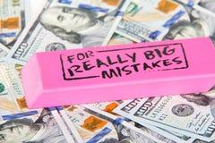Chiuda su della gomma rosa con il messaggio per l'errore realmente grande sul sparso su cento banconote in dollari fotografia stock libera da diritti