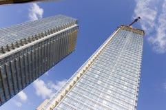 Chiuda in su della gru in cima all'alta costruzione di aumento Fotografia Stock