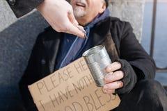 Chiuda su della latta della tenuta dell'indigente per le monete Fotografie Stock