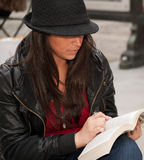 Chiuda in su della lettura urbana della donna nella città Fotografia Stock