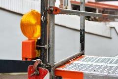 Chiuda su della luce di avvertimento arancio del riflettore allegata all'impalcatura al cantiere immagini stock libere da diritti