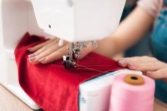 Chiuda su della macchina per cucire La ragazza alla fabbrica dell'indumento sta cucendo il nuovo vestito fotografie stock