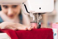 Chiuda su della macchina per cucire La ragazza alla fabbrica dell'indumento sta cucendo il nuovo vestito immagine stock libera da diritti