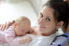 Chiuda su della madre che tiene sua figlia sveglia del bambino immagine stock libera da diritti