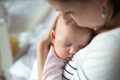 Chiuda su della madre che tiene sua figlia sveglia del bambino immagini stock libere da diritti