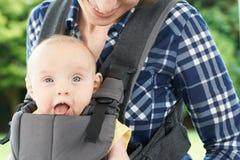 Chiuda su della madre con la figlia del bambino in trasportatore Fotografia Stock Libera da Diritti