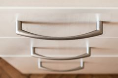 Chiuda su della maniglia del metallo di un cassetto Cassettone di legno moderno di colore leggero Concetto di mobilia domestica m fotografia stock libera da diritti