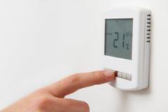 Chiuda su della mano che regola il termostato Co del riscaldamento centrale di Digital Immagine Stock