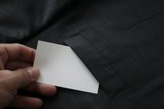 chiuda su della mano che seleziona il biglietto da visita in bianco dal buttero grigio del vestito immagine stock libera da diritti