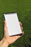 Chiuda su della mano che tiene il blocco note in bianco, sul backgroun verde del campo Fotografie Stock Libere da Diritti