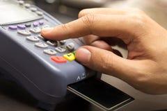 Chiuda su della mano con il colpo della carta di credito tramite il terminale Fotografie Stock