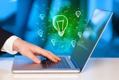 Chiuda su della mano con il computer portatile e la lampadina di idea Immagini Stock Libere da Diritti