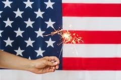 Chiuda su della mano con la stella filante sopra la bandiera americana Fotografia Stock Libera da Diritti