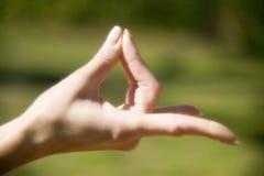 Chiuda in su della mano dei womans durante l'yoga Fotografia Stock