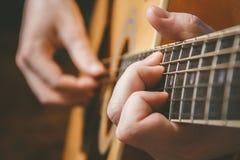 Chiuda su della mano del chitarrista che gioca la chitarra Immagini Stock