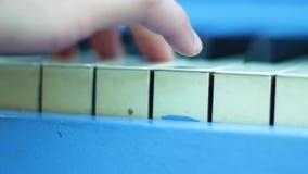 Chiuda su della mano del giocatore di piano da dietro stock footage