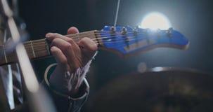 Chiuda su della mano del musicista che gioca le corde sulla chitarra elettrica archivi video