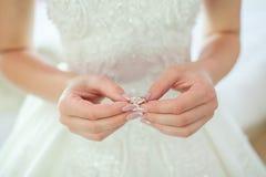 Chiuda su della mano del ` s della donna che tiene l'anello di diamante elegante con la piuma ed il fondo grigio della sciarpa Di fotografia stock