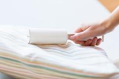 Chiuda su della mano della donna con pulizia appiccicosa del rullo fotografia stock