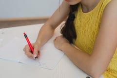 chiuda su della mano della ragazza con la penna che fa il per la matematica, disegnando il triangolo Fotografie Stock