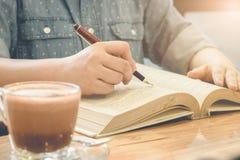Chiuda su della mano dello studente che legge un libro al tono dell'annata delle biblioteche Fotografia Stock