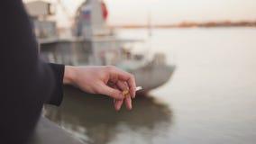Chiuda su della mano di un uomo che tiene una sigaretta di fumo accanto ad una barca sull'acqua stock footage