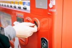 Chiuda su della mano della donna che inserisce la moneta nel distributore automatico Fotografie Stock