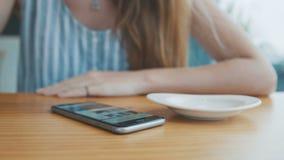 Chiuda su della mano facendo uso del telefono cellulare mentre bevono il caffè in caffè video d archivio