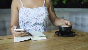 Chiuda su della mano facendo uso del telefono cellulare mentre bevono il caffè in caffè stock footage