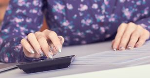 Chiuda su della mano femminile del banchiere o del ragioniere che effettua i calcoli Risparmio, finanze e concetto di economia fotografie stock libere da diritti