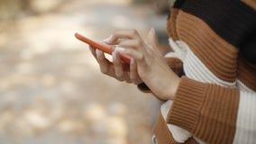 Chiuda su della mano femminile facendo uso del telefono, all'aperto archivi video
