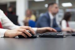 Chiuda su della mano femminile sul topo mentre scrivono sulla tastiera Immagine Stock