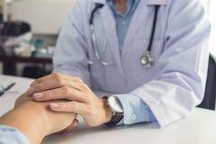 Chiuda su della mano paziente commovente di medico per incoraggiamento e la e immagini stock libere da diritti