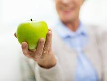 Chiuda su della mano senior della donna che tiene la mela verde Fotografia Stock