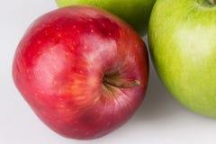Chiuda su della mela rossa con le mele verdi su bianco immagine stock libera da diritti
